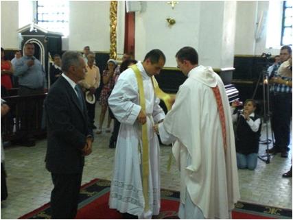 El p. Geovanny revistiéndose de los ornamentos sacerdotales