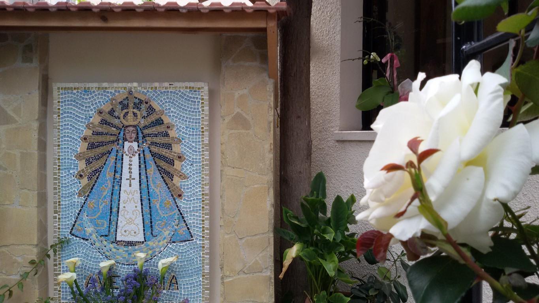 Un toque maternal : la primera rosa del arco frente al mosaico abrió el 8 de mayo.