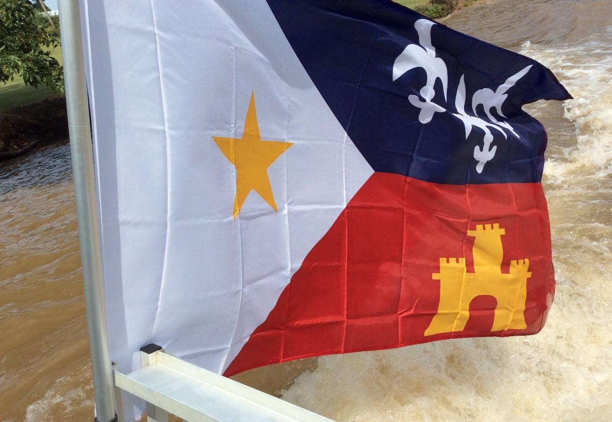 Bandera de la Diócesis de Lafayette: la Estrella amarilla de la Virgen María; la flor lily de Francia y la Torre de España.